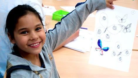 Una niña del Núñez mostrándonos las mariposas que acaba de dibujar